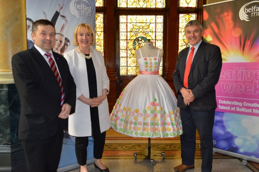 Marie Therese McGivern Principal and Chief Executive of Belfast Metropolitan College, presents one of the stunning designs showcased at the Fashion Show to Committee Chairperson Robin Swann MLA (left) and Deputy Chairperson Tom Buchanan MLA
