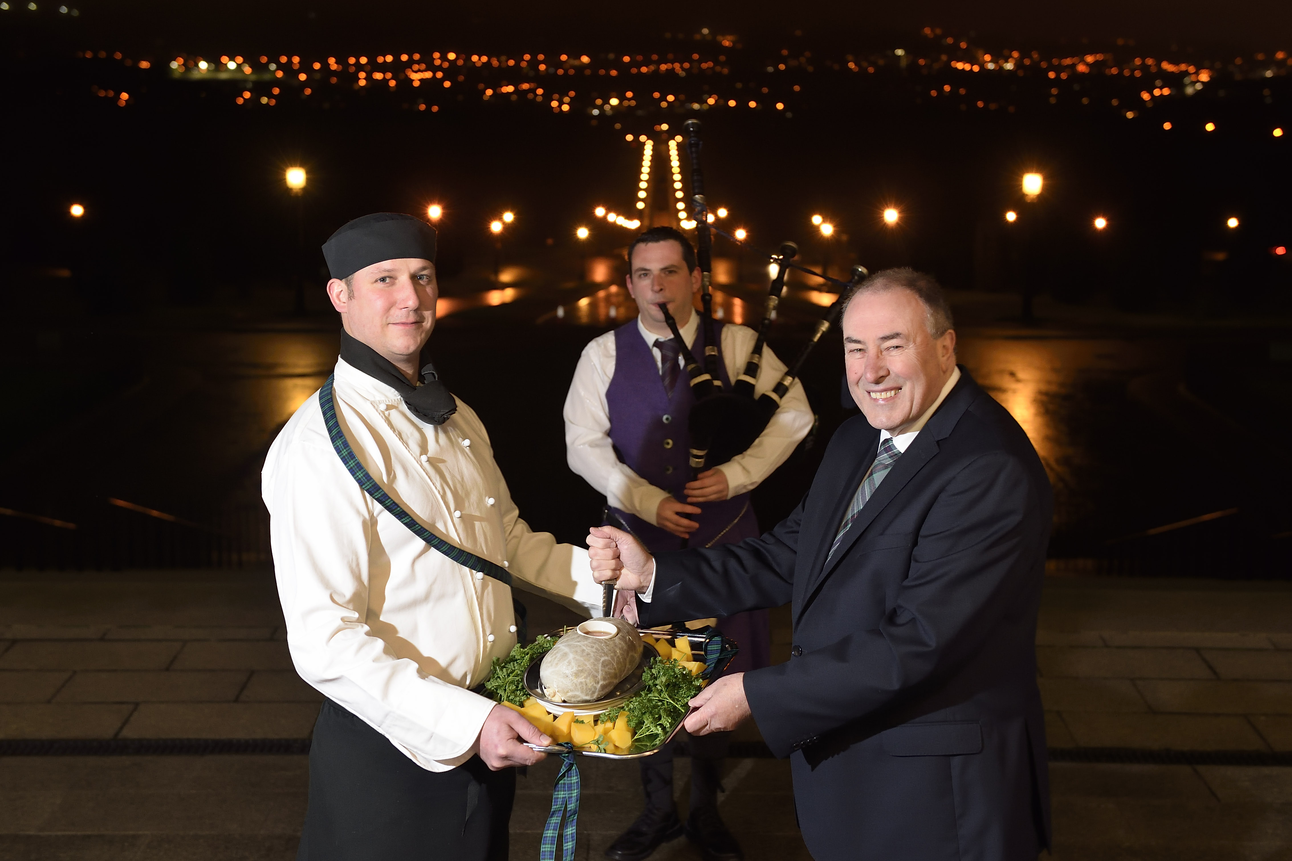The Speaker of the Assembly, Mitchel McLaughlin MLA, pictured with Piper Darren Milligan and chef, Ashley McMahon presenting the haggis, at the first official Burns Night celebration in Parliament Buildings. The celebration of Scotland's national poet, Robert Burns, took place in the Great Hall. Picture: Michael Cooper